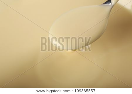 Background of condensed milk and a spoon in a bowl, close-up