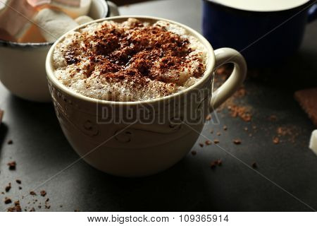 Cup of coffee with milk on a wooden table closeup