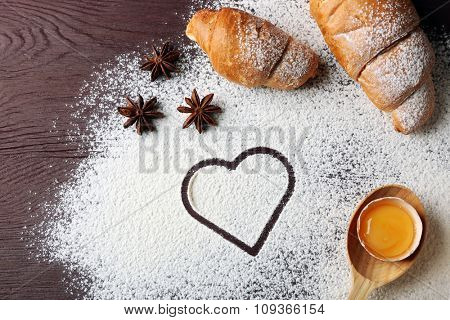 Heart of flour, croissant and spices on gray background