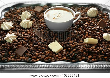 Cup of coffee with sweets and coffee beans on a tray