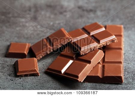 Milk chocolate pieces on gray background