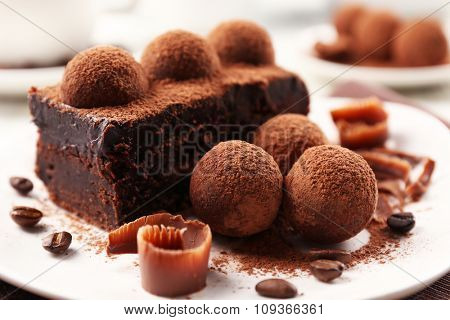 Slice of chocolate cake with a truffle on plate closeup