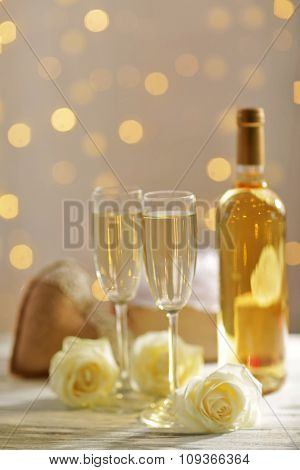 Glasses of wine, a bottle, a white rose and a gift in the box, on blurred background