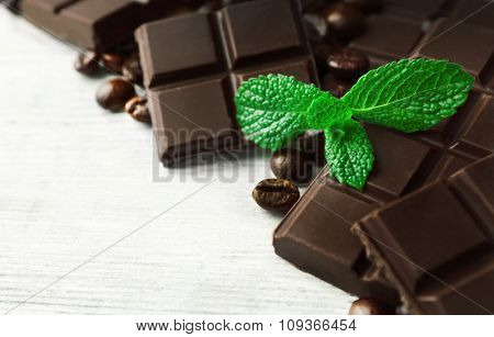Black chocolate pieces and mint leaves on color wooden background