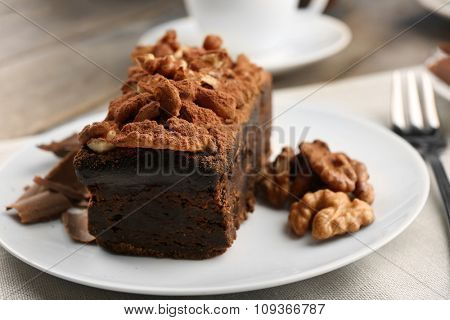 A piece of chocolate cake with walnut on the table, close-up