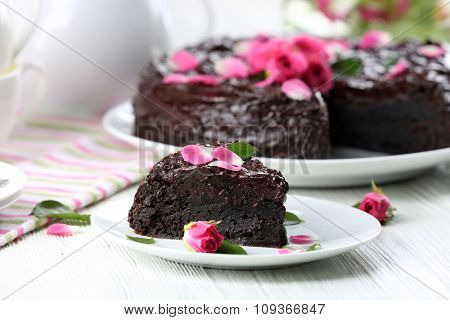 Piece of chocolate cake decorated with flowers on white wooden table