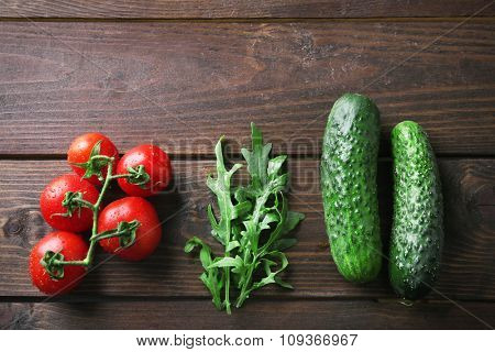 Tomatoes, cucumber and arugula on wooden background