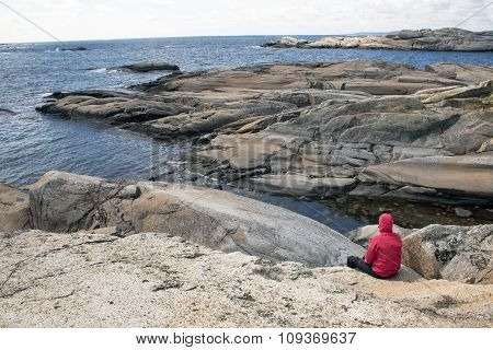 Lonely man sitting at the rock and looking on sea.