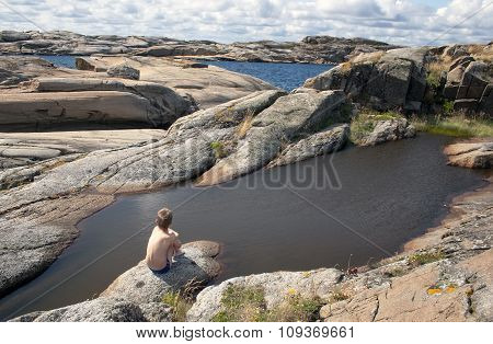 Young boy sitting at the rock and looking on sea.