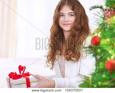 Portrait of adorable girl celebrating New Year at home near Christmas tree, receiving gift box, enjoying festive surprise