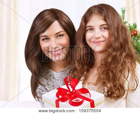 Portrait of happy teen girl with her beautiful young mother celebrating winter holidays at home, enjoying Christmas present