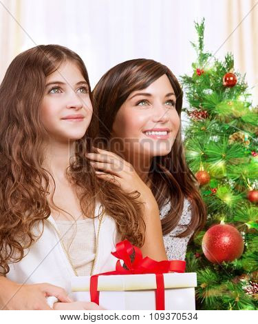 Portrait of cheerful mother and daughter with wonder looking up, celebrating holidays near beautiful decorated Christmas tree, with pleasure receiving festive gift box