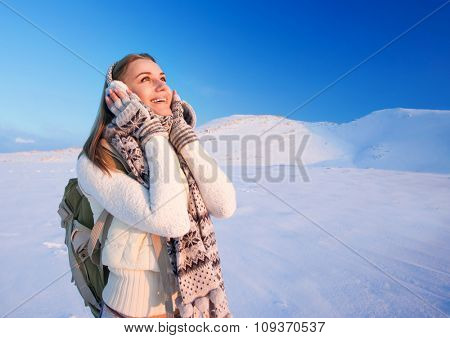 Cute excited girl holding head by hands with wonder looking up, enjoying beautiful winter mountains view, happy active wintertime holidays