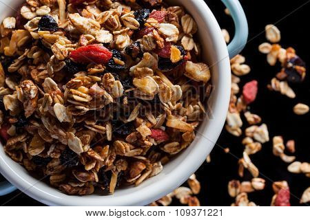 Granola in a bowl on black from above closeup