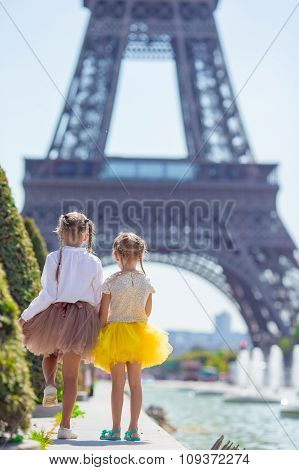 Adorable little girls in Paris background the Eiffel tower during summer vacation