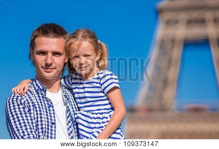 Happy father and little adorable girl in Paris near Eiffel Tower during summer french vacation