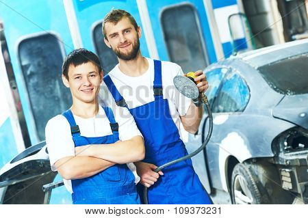 portrait of two smiling auto mechanic workers with power buffer machine  at automobile repair and renew service station