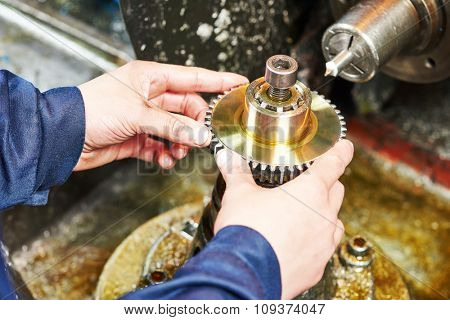 metalworking industry. Operator hands installing tooth gear cogwheel for machining by cutting mill tool.