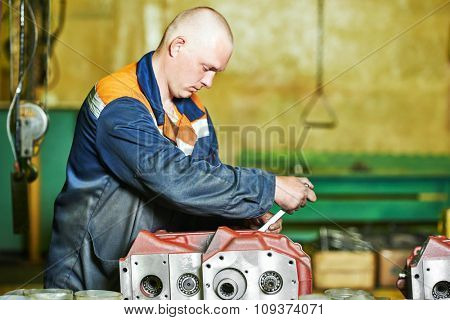 Factory industrial worker assembling the reduction gear box on production line manufacturing workshop