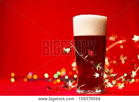 Full glass of bear or ale with tinsel and christmas lights on red background
