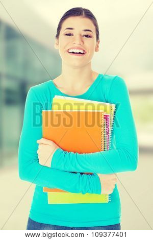 Beautiful young woman student with workbook