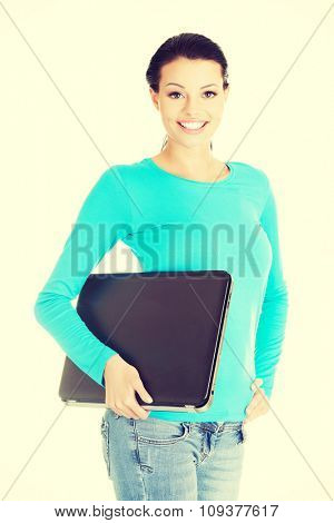 Happy woman holding a laptop.