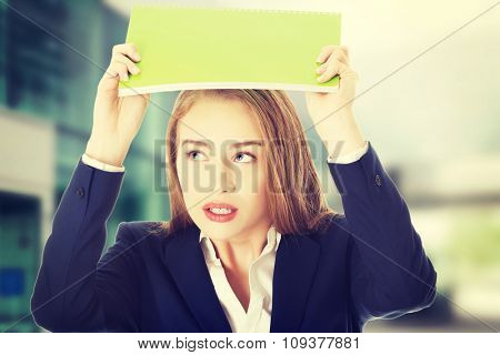 Beautiful caucasian woman is holding notebook over her head.