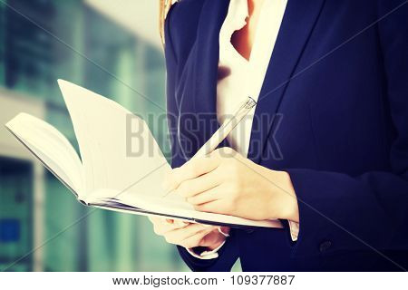 Close up on notebook and pen in business woman's hands