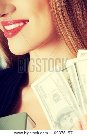 Portrait of a woman holding a clip of dollars