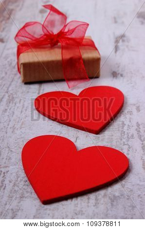 Red Hearts And Wrapped Gift For Valentines Day On Old Wooden Table