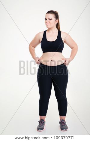 Full length portrait of a woman pinches fat on her belly isolated on a white background