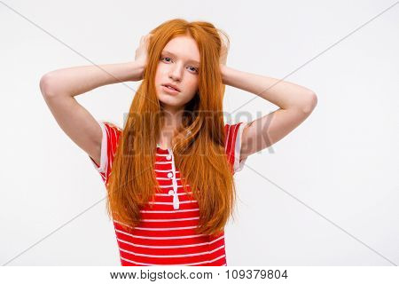 Thoughtful pretty sensual redhead female with long beautiful hair holding head in hands and posing on white background