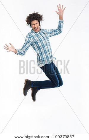Full length portrait of a cheerful afro american man in headphones jumping isolated on a white background