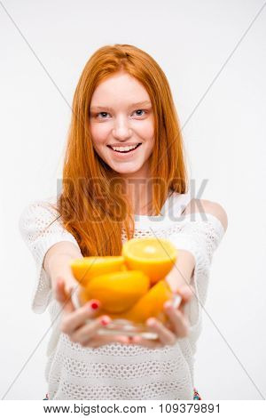 Positive excited beautiful natural young redhead woman offers oranges posing on white background