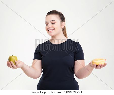 Portrait of a happy fat woman choosing between donut and apple isolated on a white background