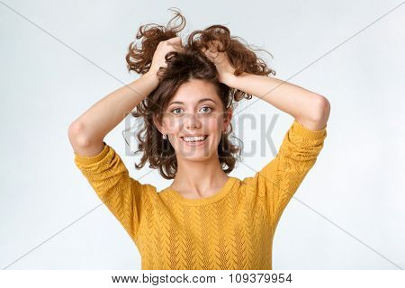 Portrait of a smiling casual woman holding her hair isolated on a white background