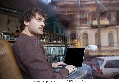 Pensive handsome curly young man in brown sweeshirt using laptop with blank screen sitting in cafe
