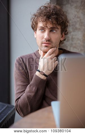 Thoughtful attractive handsome curly pencive distracted guy in brown sweetshirt sitting and dreaming