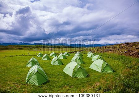 Campground athletes. Green tent on a grassy lawn. July in Iceland