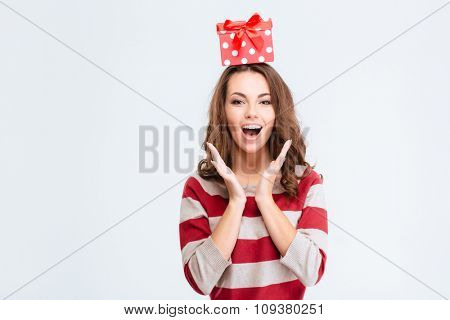 Portrait of a cheerful amazed woman with gift box on head looking at camera isolated on a white background