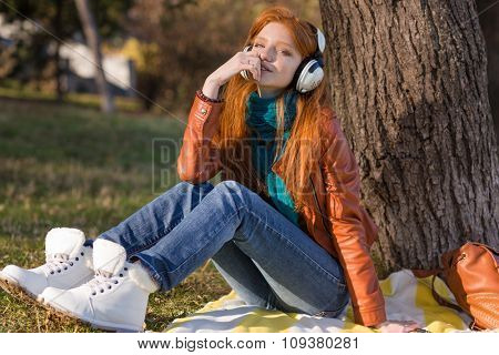 Pretty pensive young woman in leather jacket, white boots and jeans listening to music under the tree