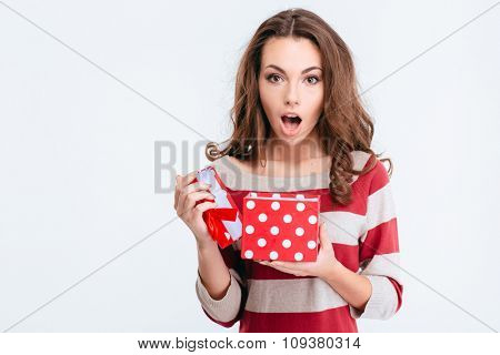 Portrait of a pretty amazed woman holding gift box isolated on a white background