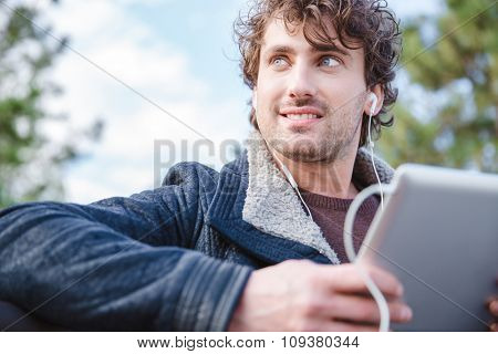 Handsome attractive smiling happy joyful young male in black jacket using tablet and looking away
