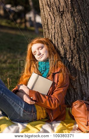 Beautiful carefree young redhead lady in leather jacket and jeans sleeping under the tree in park
