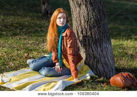 Young attractive pensive woman with beautiful red hair in leather jacket sitting under the tree in the park