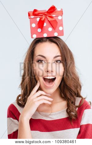 Portrait of a happy amazed woman with gift box on head looking at camera isolated on a white background