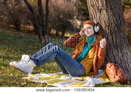 Attractive relaxed young lady listening to music sitting under the tree in the park