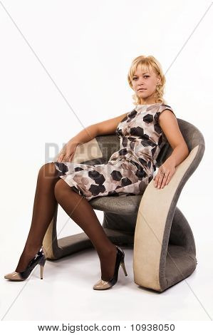 Beautiful Woman Sits In An Armchair