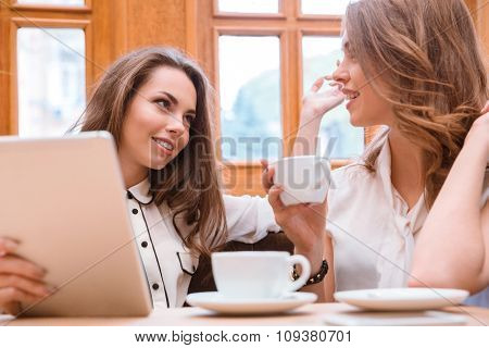 Portrait of a girlfriends drinking coffee and speaking in cafe
