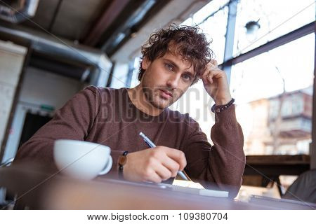 Concentrated attractive thoughtful curly pensive young male in brown sweetshirt sitting and writing in cafe